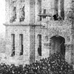 The crowd mobs the steps of the city hall, while the windows are filled with men