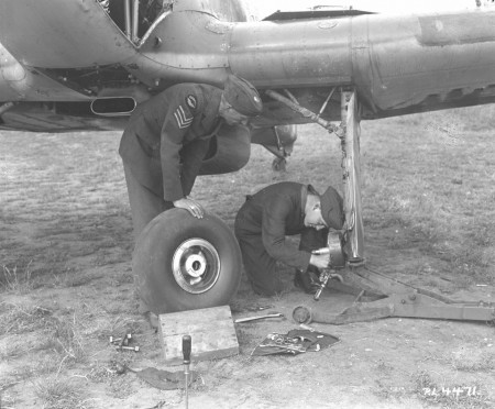 Ground crew replace the port wheel on a Hurricane.  These often forgotten, yet vital members of the RCAF, played an important role throughout the war